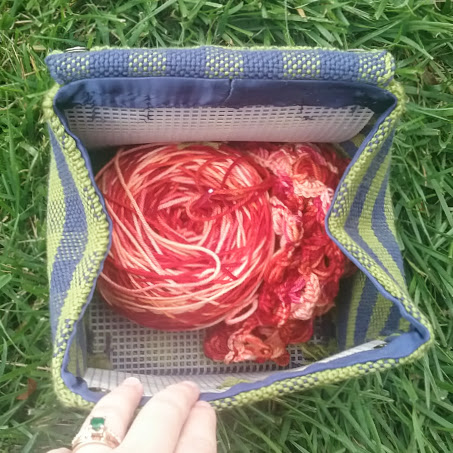 handwoven blue and green plaid bag with yarn inside