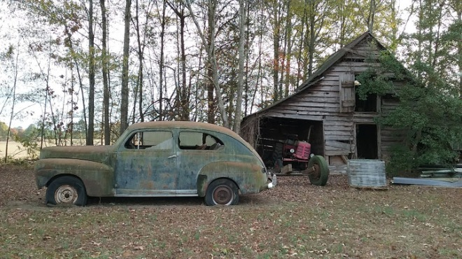 old wooden barn with rusted car